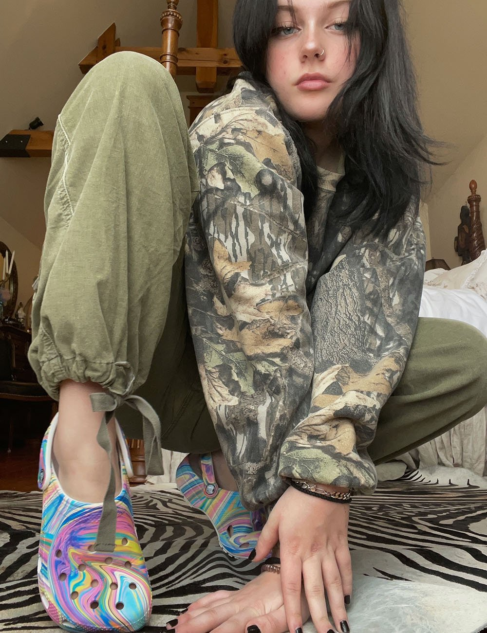 Girl wearing marbled pastel-color Crocs with an all camouflage outfit.