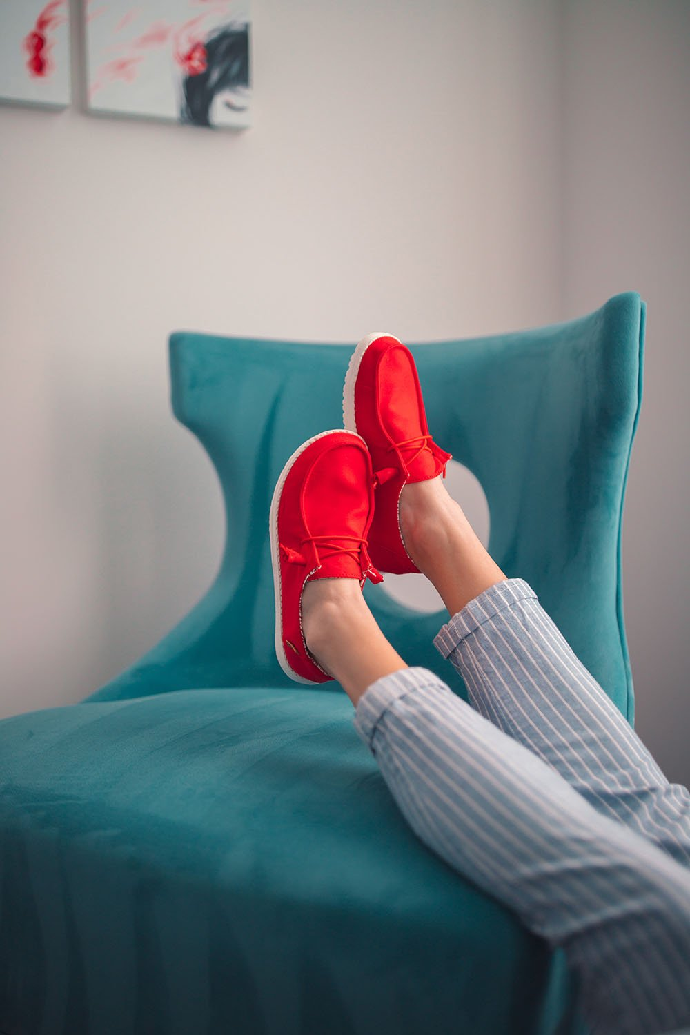 Legs kicked back wearing red Hey Dude Wendy casual shoes.