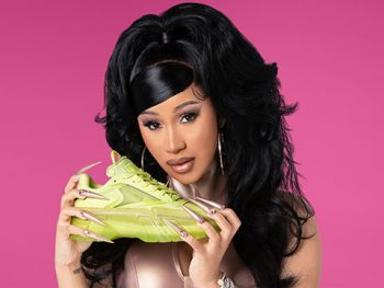 Cardi B Holds a Yellow Reebok Club C Sneaker.